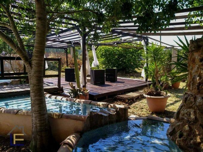 gemütliche Veranda mit vielen Pflanzen und Brunnen