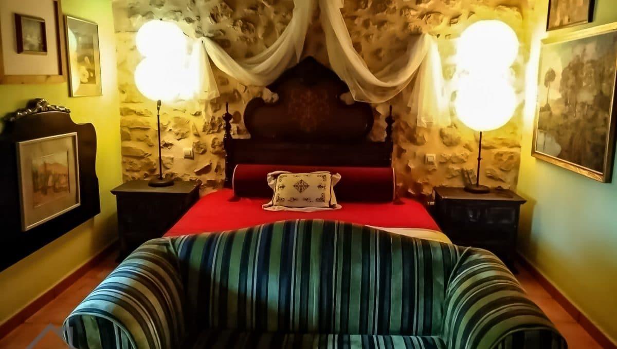 rustikales Schlafzimmer mit Steinmauer