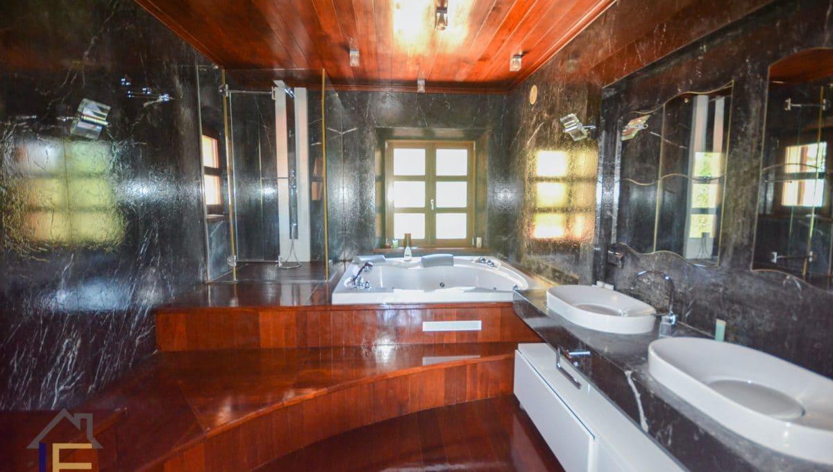 Badezimmer mit Whirlpool und Dusche aus Holz und Marmor