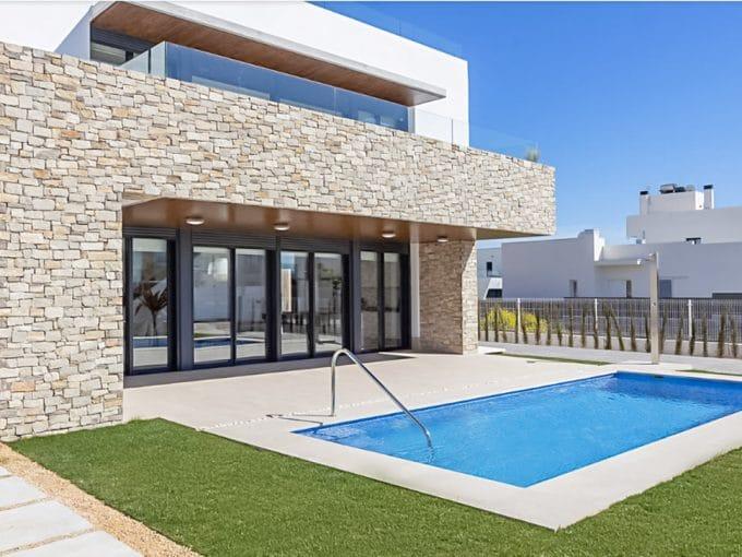 Helle Pool terrasse mit gras und steinwand