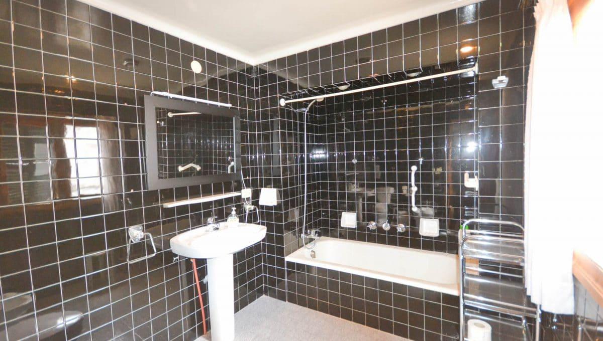 Badezimmer mit Badewanne mit schwarze Fliesen